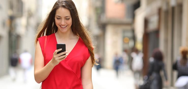 Mujer sonríe mientras mira su teléfono